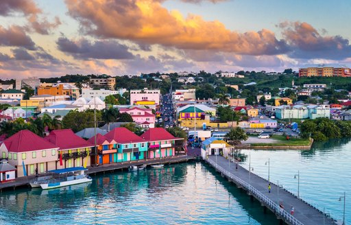 Caribbean town on edge of water with bridge stretching out and cloudy sky above