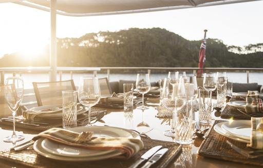 al fresco dining table is set up for dinner on the upper deck aft of charter yacht RELENTLESS