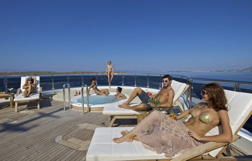 Guests gathered around the Jacuzzi on board luxury yacht O'MEGA