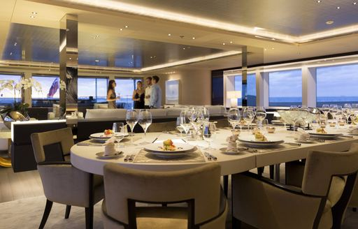 table set for dinner with guests socializing in the lounge on board charter yacht NAUTILUS