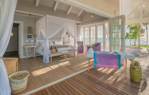villa suites on thanda island, with doors leading to terrace and canopied bed in centre