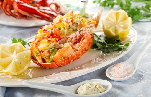 A plate with a halved and dressed lobster and lemons, a traditional Sardinian meal