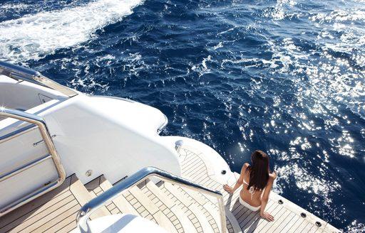 girl sits on the swim platform of luxury yacht spirit