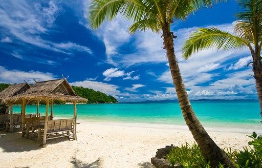 Beach scene, Siam Bay, Ko Racha Yai, showing basic beach huts and palm trees facing the sea