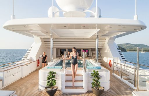 Woman poses on superyacht TITANIA's upper deck with large spa pool in background