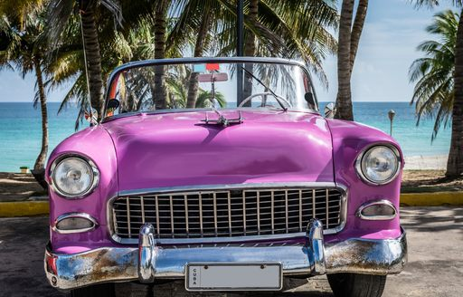 pink vintage car on the beach in cuba