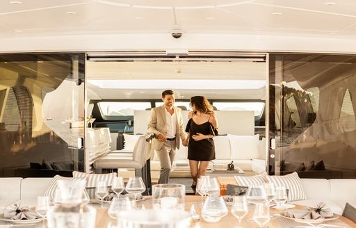 superyacht dining on the interior, couple walk towards table on charter