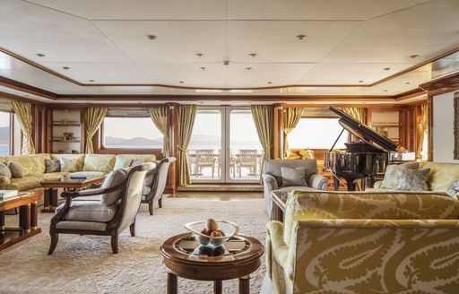 Main salon on board charter yacht TITANIA, with grand piano in background