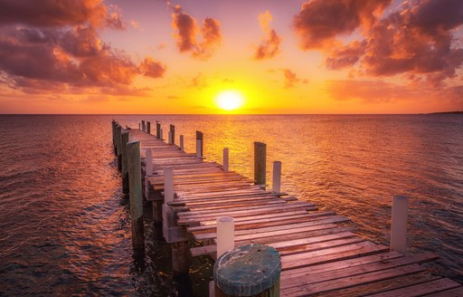 Dock during caribbean sunset, beautiful magenta colors and perspective of this boat dock and fishing dock in Eleuthera island