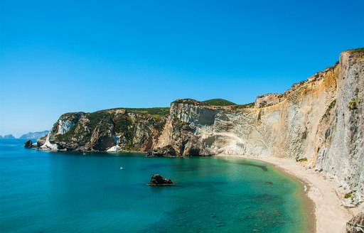 secluded sandy beach backed by cliffs and lapped by turquoise waters on Isola di Ponza, Italy