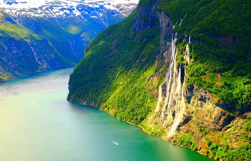 The steep and green landscape of the Norwegian fjords.