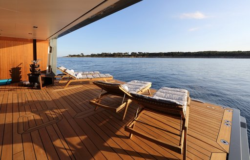 beach club and swim platform on admiral yachts planet nine, with sun loungers lined up next to the water