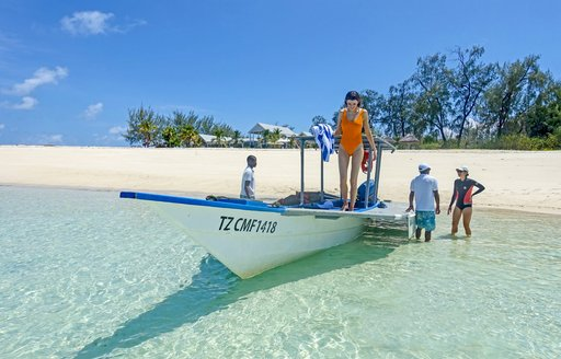 woman in yellow swimsuit stands on boat looking at the shallow water below on thanda island