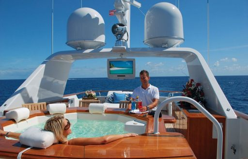 Woman lounging inside a designer jacuzzi while she is being served cocktails by the crew of charter yacht Lady J