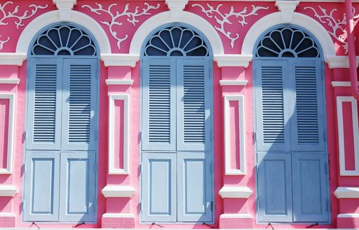 Historic pink shop-house facade in Phuket Town, showing three blue shuttered windows