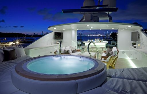 night shot of lit-up jacuzzi pool on superyacht alessandra, with bar and seating in background