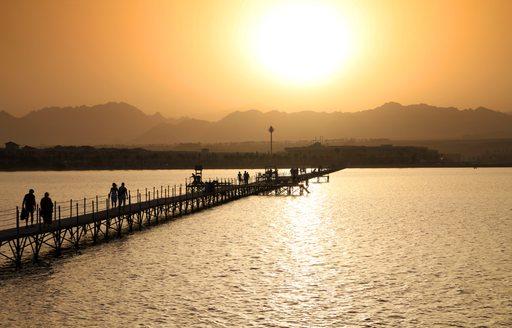 Long bridge over calm water at sunset