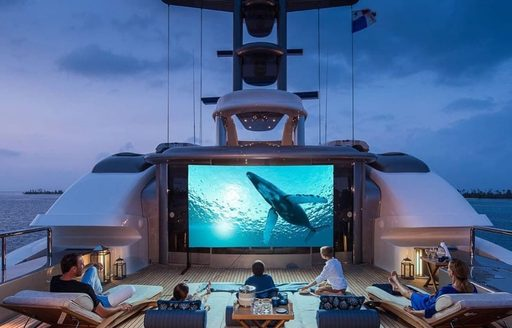Charter guests watch film alfresco on aft deck of yacht