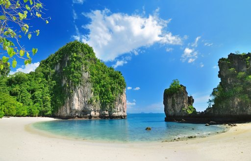 idyllic beach in Thailand with white sand and limestone rock formations
