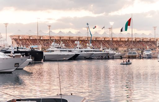 Superyachts in foreground at Yas Marina during F1 Abu Dhabi Grand Prix with grandstands in background