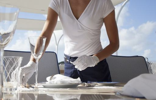 Chief stewardess on board superyacht polished cutlery and glasses while wearing white gloves on board superyacht
