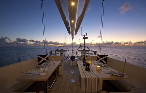 cockpit for sailing yacht PTARMIGAN is set for dinner as the sun sets over the horizon