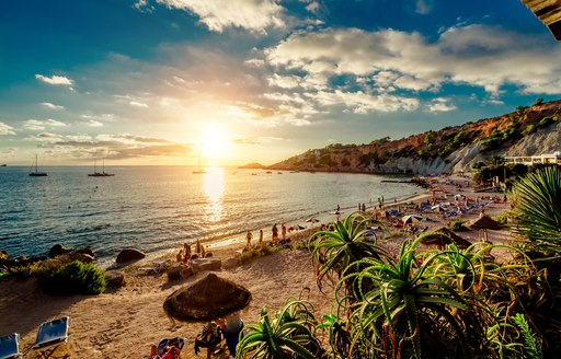 People sunbathing on sandy beach in Ibiza as sun sets