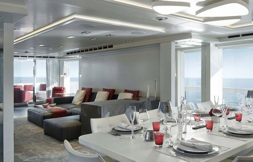 THE DELUXE AND SLEEK SINING ARANGEMENT IN THE MAIN SALON OF CHARTER YACHT home OVERLOOKING THE WATER FROM HER large windows