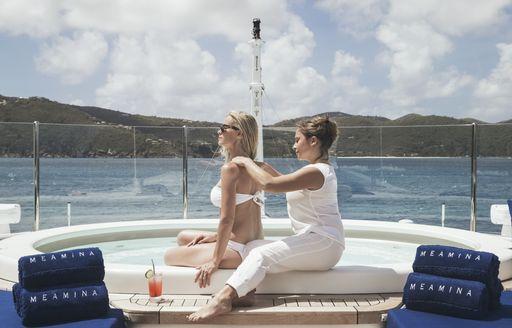 female charter guest enjoys massage on the sundeck Jacuzzi of motor yacht MEAMINA