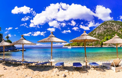 White sand beach in Greece, overlooking shallow blue waters with sun loungers and umbrellas lined up on the shore