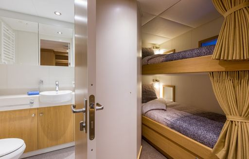 Bunk beds in Game Changer yacht, with door open to bathroom and sink visible