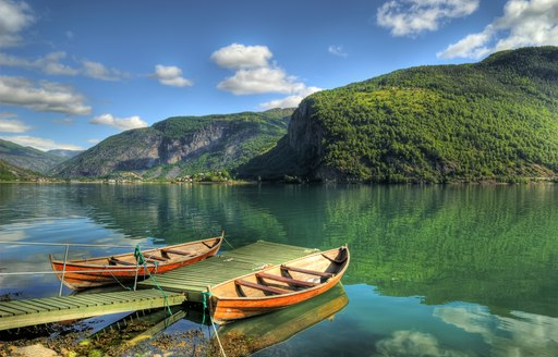 A canoe sat on the water running through the Norwegian fjords