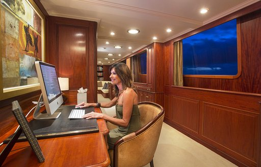 Woman using an imac inside the professional and versatile office of charter yacht Lady J