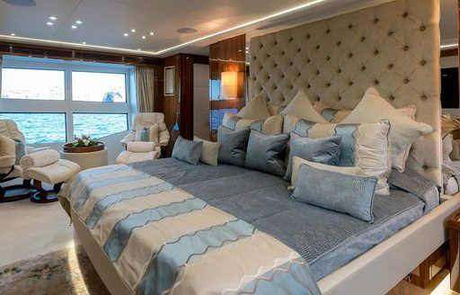 Owner's cabin on board superyacht ANYA, with bright windows and blue bedding