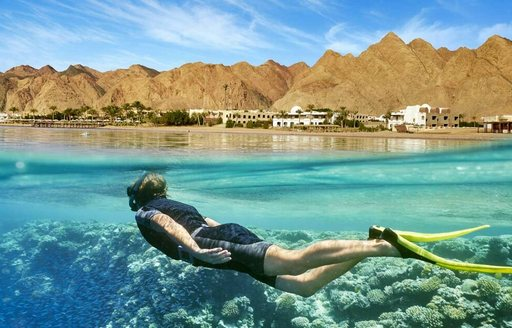 Charter guest snorkelling in the Red Sea, glimpse of corals under water and old settlement against mountainous terrain in background