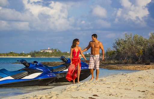 Couple romantically walking down the sandy coast of a island in the British virgin islands after they arrived via their jet skis from the superyacht Lady J