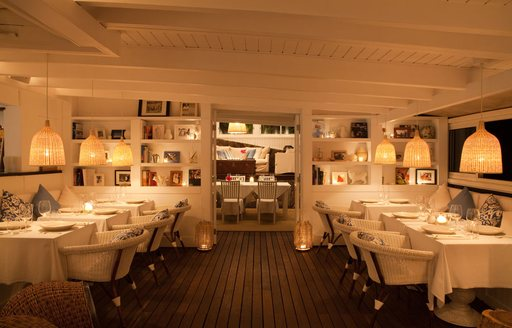 The white tables and dark wood flooring inside Bonito