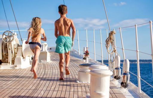 Two children running on the deck of a classic yacht from behind