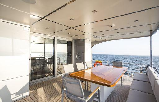 shaded al fresco dining area on board motor yacht Timeless