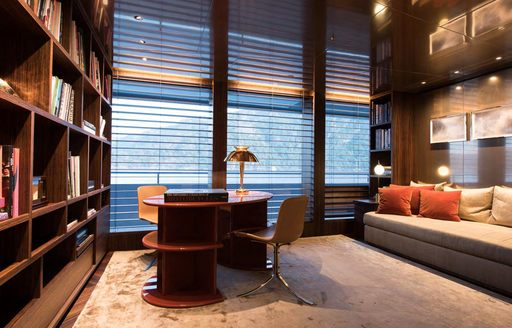 Elegant office area on superyacht SAVANNAH, with ambient lighting and sofa visible