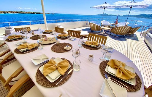 Dining table laid out on deck on superyacht LIONSHARE