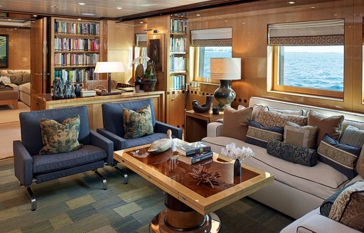 Main salon onboard Superyacht LIND, L shaped sofa and armchairs around a coffee table, with bookshelves in background