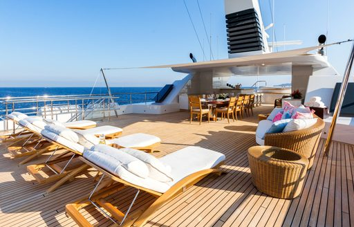 Feadship charter yacht W sundeck with loungers and dining area