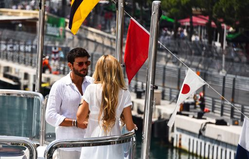 Man and woman stand on bow of a luxury yacht having a chat, with race circuit visible in background