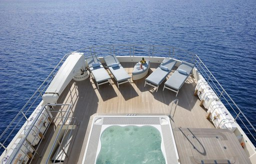 A charter guest stretching out on a sunlounger nearby to the Jacuzzi on board superyacht SERENITAS II