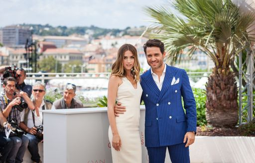 Man and woman at Cannes Film Festival infront of superyachts in marina