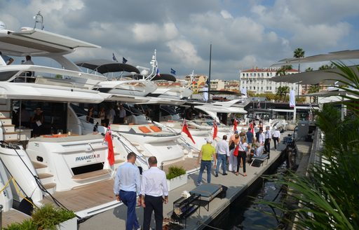 People walk past luxury yachts at Cannes Yachting Festival