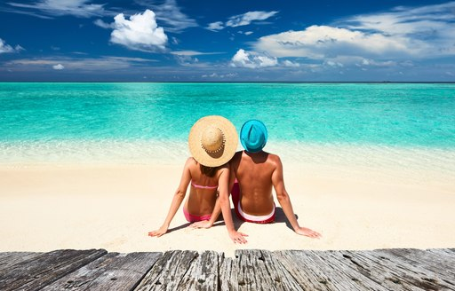 man and woman relax together on a white-sand beach in the Maldives