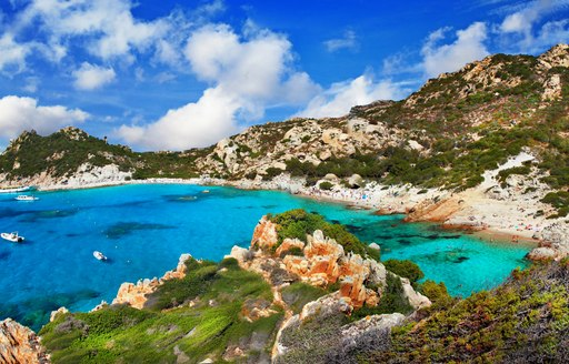 turquoise water in bay in italy, with sandy beach behind