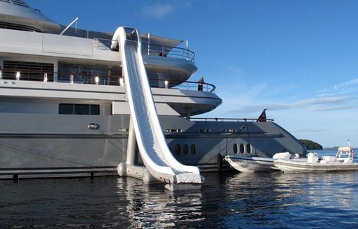 Charter yacht TV with inflatable water slide and two of her tenders